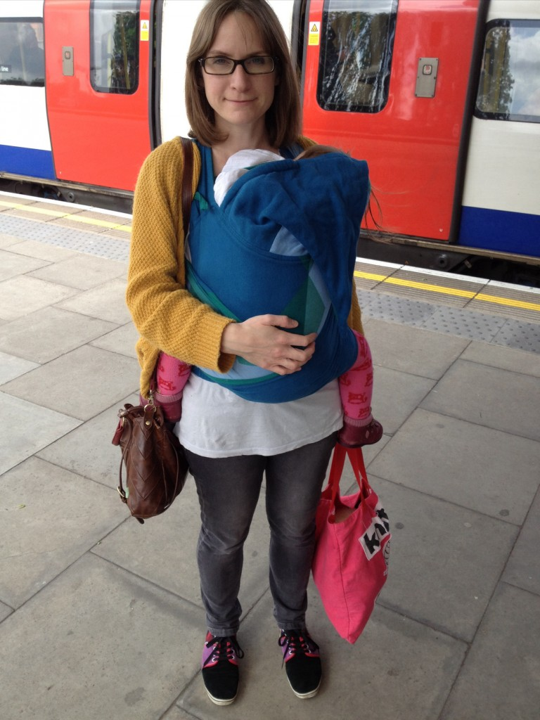 Photo shows a white woman carrying her baby on her front in a blue sling. In the background is a London underground train